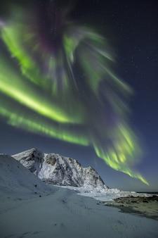 Colpo verticale delle montagne innevate sotto la bella aurora boreale nel cielo
