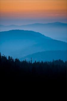 Colpo verticale di alba con belle tonalità pastelli di blu e arancione