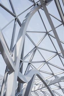 Colpo verticale di angolo basso del soffitto degli edifici geometrici bianchi