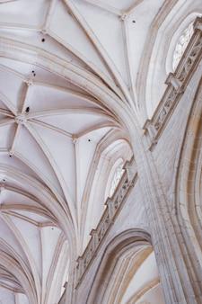 Colpo verticale di angolo basso delle colonne bianche e del soffitto di una vecchia costruzione