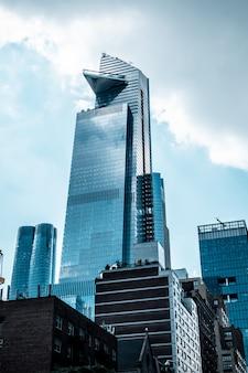 Colpo verticale di angolo basso delle costruzioni di vetro moderne di affari che toccano il cielo