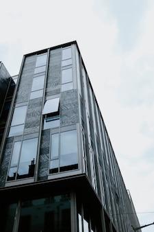 Colpo verticale di angolo basso di bella costruzione di vetro catturata durante il giorno
