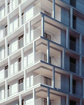 Colpo verticale di angolo basso di un alto edificio bianco di cemento