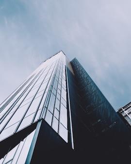 Colpo verticale di angolo basso di un grattacielo in una facciata di vetro