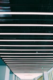 Colpo verticale di angolo basso di un soffitto in un corridoio con le illustrazioni bianche