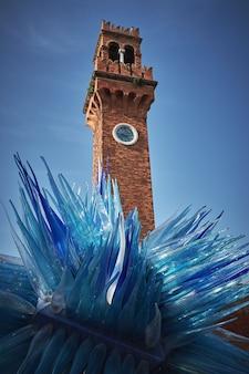 Colpo verticale di angolo basso di una torre e di una scultura blu a murano, italia