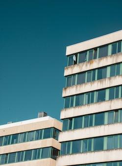 Colpo verticale di angolo basso di vecchia costruzione con le finestre rotte sotto il cielo blu