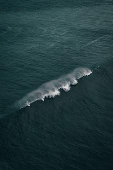 Colpo verticale di belle onde di oceano forti in collisione un giorno nuvoloso