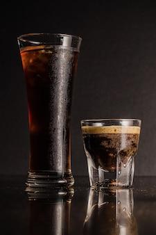 Colpo verticale di bicchieri di liquore e caffè con riflessi