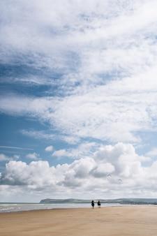 Colpo verticale di due persone a cavallo lungo la riva della spiaggia sotto un cielo nuvoloso in francia