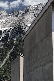 Colpo verticale di edifici grigi vicino alle montagne circondate da alberi