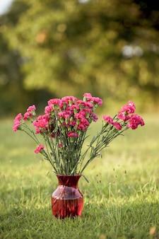 Colpo verticale di fiori rosa in un vaso di vetro su un campo erboso