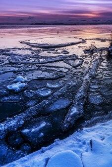 Colpo verticale di ghiaccio e neve sulla spiaggia durante un tramonto