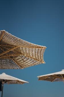 Colpo verticale di ombrelloni in legno marrone