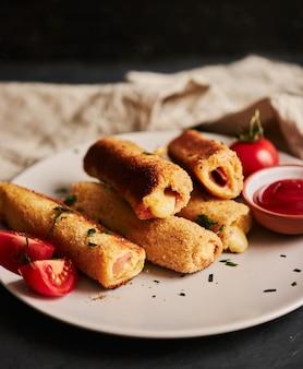 Colpo verticale di pane tostato rotoli con prosciutto e formaggio e pomodori e ketchup su un piatto bianco