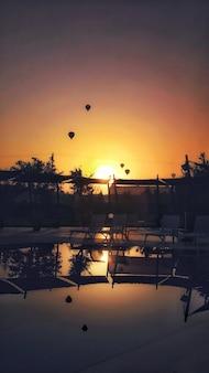 Colpo verticale di paracadute che volano durante un tramonto mozzafiato