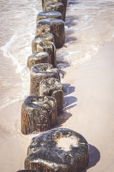 Colpo verticale di piccole assi di legno su una spiaggia sabbiosa