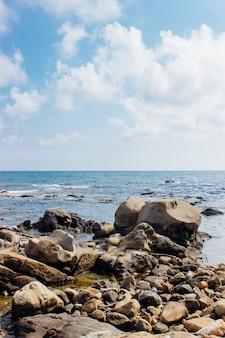 Colpo verticale di rocce in riva al mare sotto il cielo nuvoloso