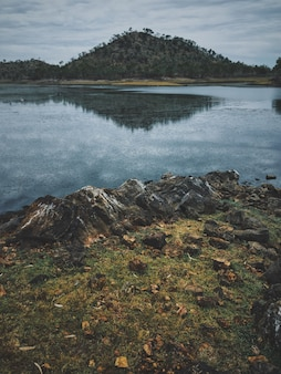 Colpo verticale di rocce vicino all'acqua che riflette la montagna