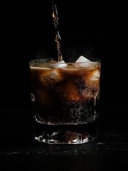Colpo verticale di soda che viene versato in un bicchiere pieno di ghiaccio