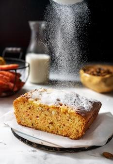 Colpo verticale di torta di carote con zucchero a velo, stile rustico