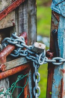 Colpo verticale di un lucchetto a catena del cancello