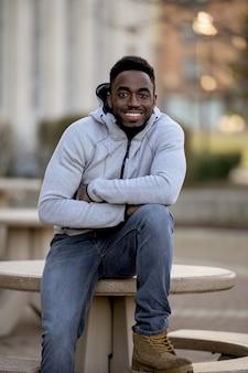 Colpo verticale di un maschio afroamericano attraente che sorride davanti alla macchina fotografica