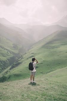 Colpo verticale di un maschio che sta in un bello campo verde un giorno soleggiato
