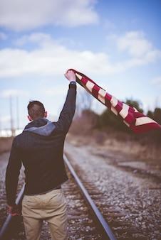 Colpo verticale di un maschio che sta sulle piste del treno mentre ostacolando la bandiera degli stati uniti