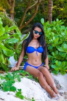 Colpo verticale di un modello femminile asiatico in bikini blu in spiaggia guardando verso il basso con modestia