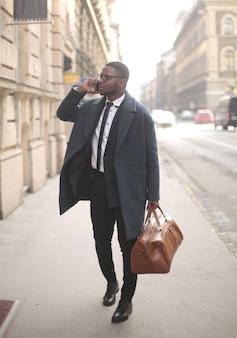 Colpo verticale di un uomo afroamericano ben vestito che parla sul telefono