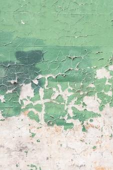 Colpo verticale di un vecchio muro verde esposto all'aria