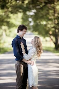 Colpo verticale di una coppia bianca felice che gode della reciproca compagnia nel mezzo di un parco