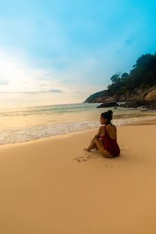 Colpo verticale di una femmina che indossa un costume da bagno rosso seduto sulla spiaggia di sabbia durante l'alba