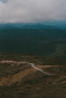 Colpo verticale di una strada fino alla montagna sotto un cielo nuvoloso