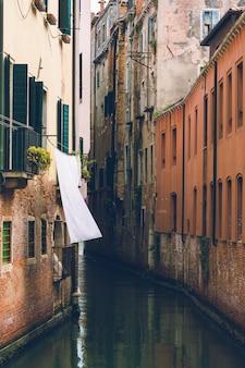 Colpo verticale di uno stretto canale d'acqua tra vecchi edifici europei. perfetto per uno sfondo.