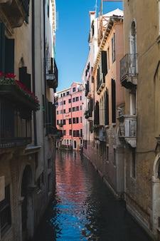 Colpo verticale di uno stretto canale nel mezzo degli edifici a venezia italia