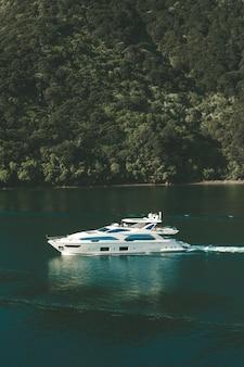 Colpo verticale di uno yacht sul corpo d'acqua in nuova zelanda