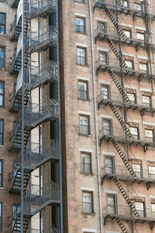 Colpo verticale di vecchie costruzioni di appartamento di pietra con le scale dell'uscita di sicurezza dai lati