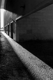 Colpo verticale in scala di grigi del sole che splende sul marciapiede attraverso gli edifici