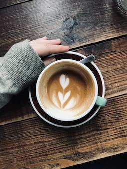 Colpo verticale sopraelevato della mano di una persona vicino al caffè di arte del latte su una superficie di legno