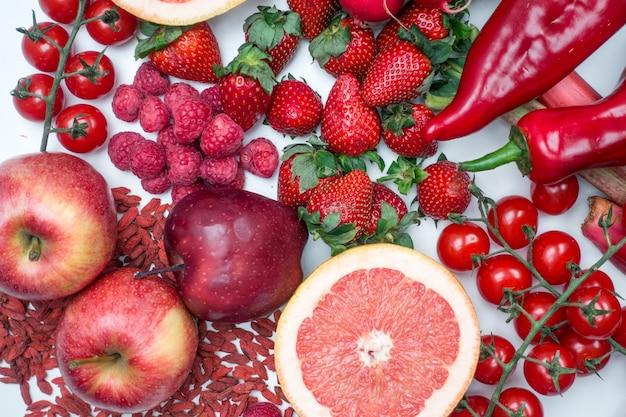Colpo vibrante aereo di frutta e di verdure rosse su una priorità bassa bianca