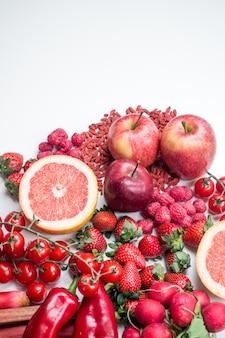 Colpo vibrante di frutta e verdure rosse su una priorità bassa bianca