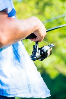 Colpo vicino del pescatore di sport che annaspa in linea sulla canna da pesca