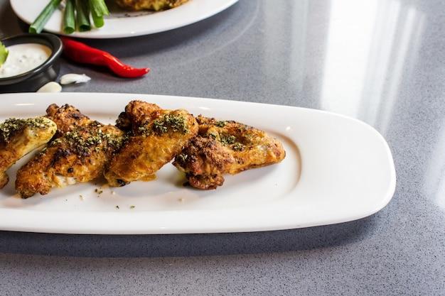 Colpo vicino delle ali di pollo fritto su un vassoio bianco lungo