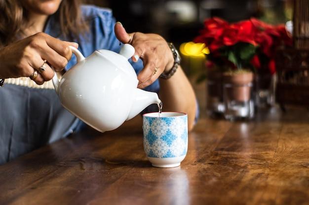 Colpo vicino di acqua di versamento femminile in una tazza con uno sfondo sfocato