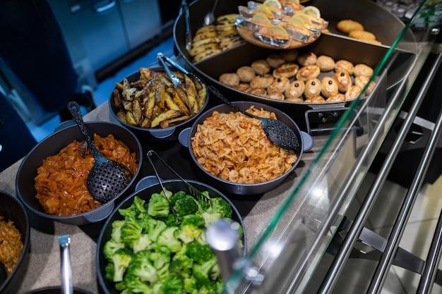 Colpo vicino di vetrine con cibo nella zona self-service del ristorante
