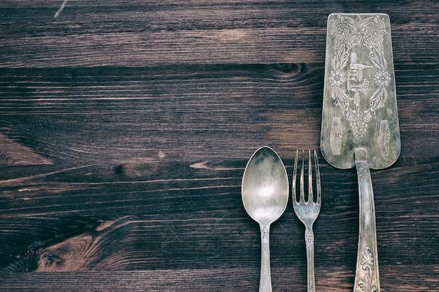 Coltelleria d'annata su fondo di legno rustico.