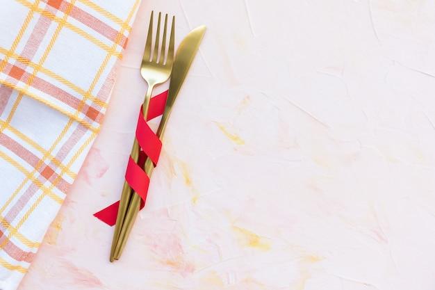Coltelleria dorata in nastro rosso e asciugamano di cucina su un rosa