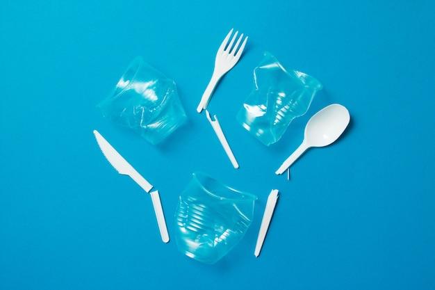 Coltelli di plastica monouso rotti bianchi, cucchiai, forchette e cannucce di plastica su uno sfondo blu.